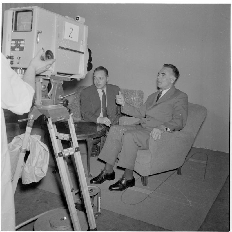 Polizeipräsident Holaubek sitzt mit einem Herrn vor Fernseh-kamera und spricht. Fernsehen - Polizeipräsident Holaubeck von Scheidl