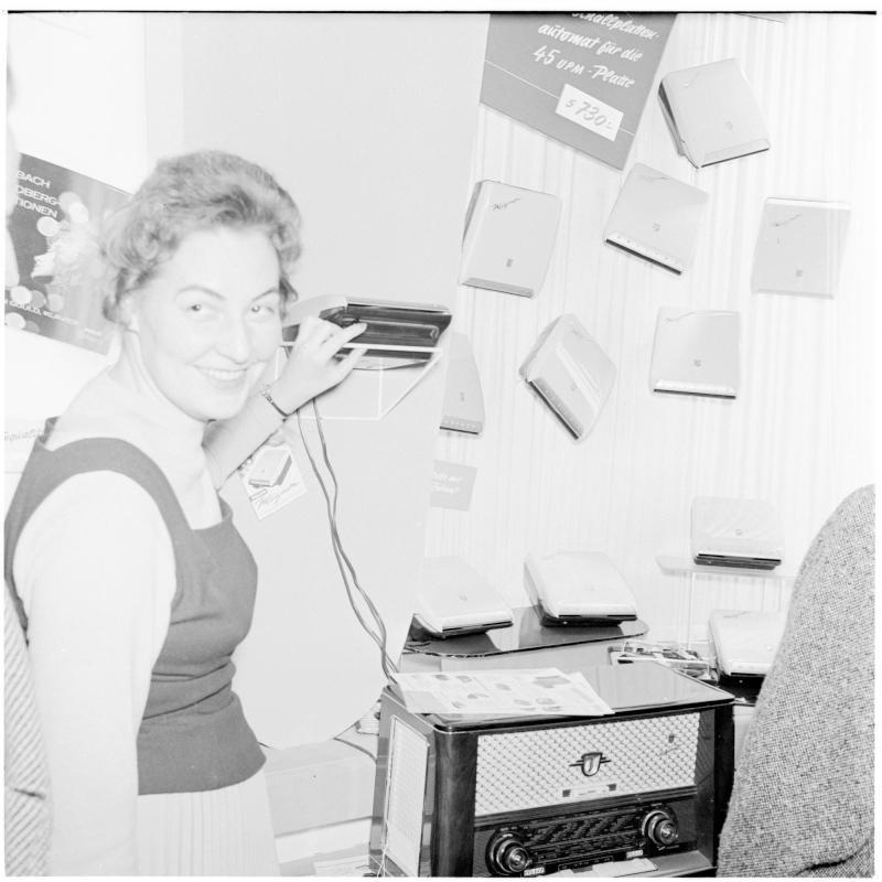 Frau zeigt Radio mit einem technischen Gerät. Fernseh-Messe von Scheidl