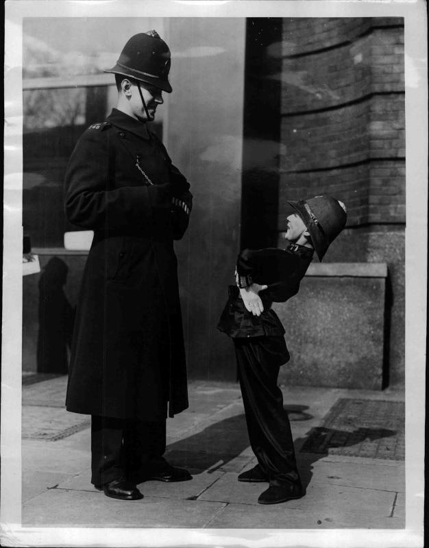 Kind als Polizist steht vor einem richtigen Polizisten, er macht bei einem Tanz-Wettbewerb mit, der sich für blinde Babies einsetzt von New York Times Photo