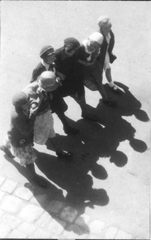 Mädchen auf der Straße, sie gehen in einer Reihe im Gleichschritt und haben sich untergehakt, ihre Schatten auf der Straße