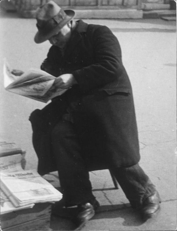 Straße, Mann auf einem Stockerl sitzend, Zeitung lesend; auf einer Kiste die neben ihm steht, liegen Zeitungen; er trägt einen dunklen Mantel und hat einen Hut auf; im Hintergrund zwei Männer im Gespräch, Gebäude
