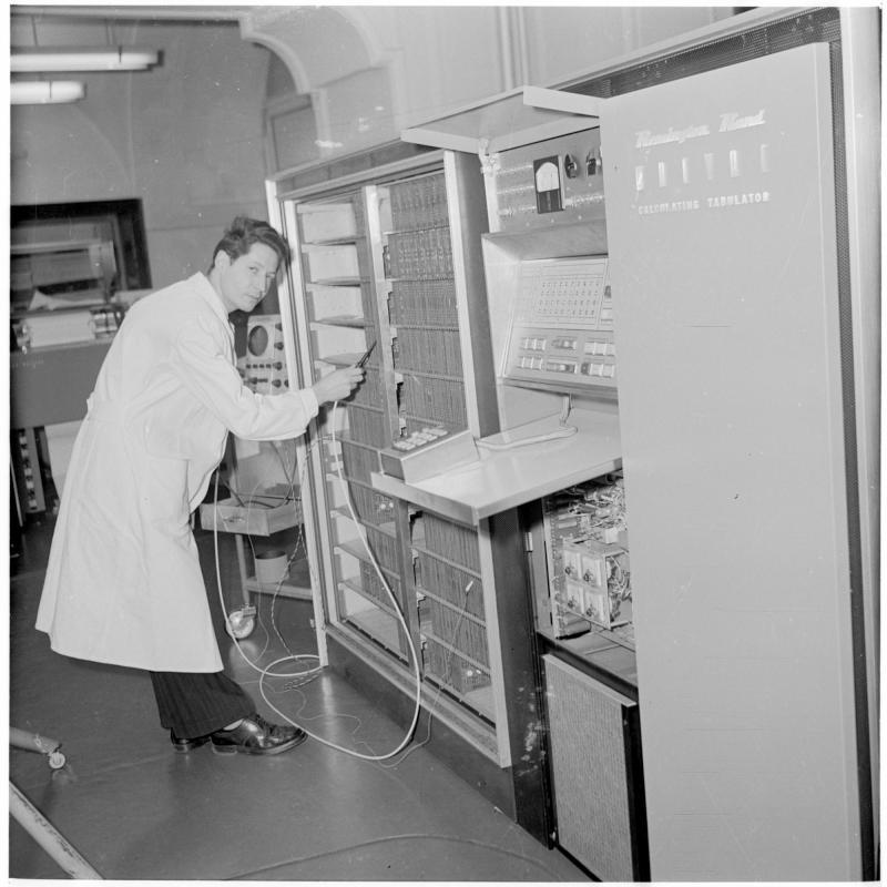 Mann steht beim Computer mit einem Gerät. Elektronische Rechenmaschine, Computer von Scheidl