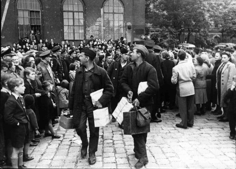 Ankunft der Heimkehrer am Südbahnhof, zwei Heimkehrer tragen Rucksäcke und Pakete mit sich, rund herum wartende Menschen