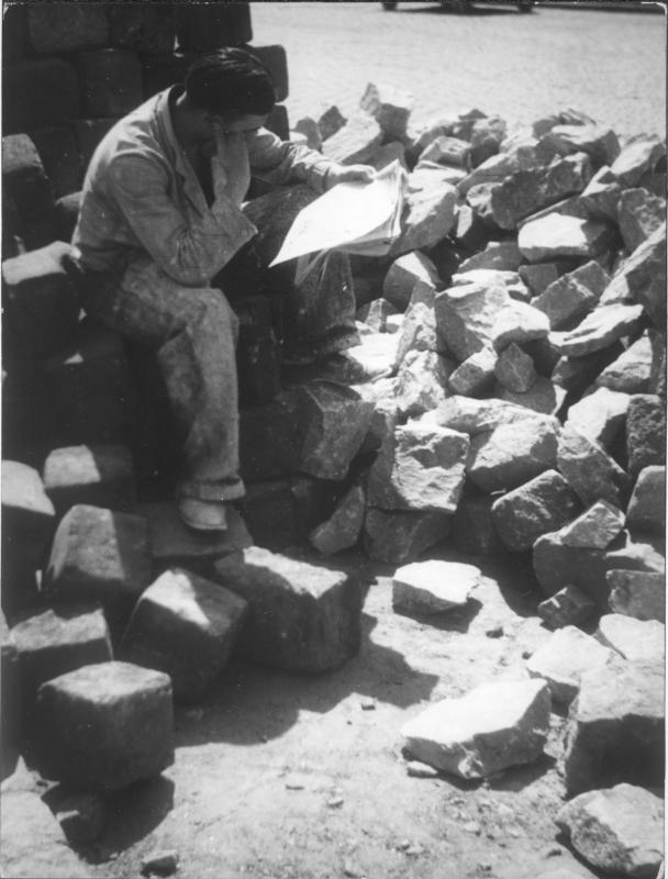 Straßen-Arbeiter macht Pause - auf Steinhaufen sitzend, Zeitung lesend