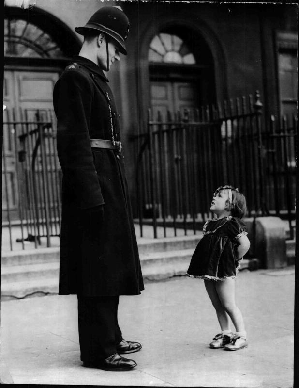 Kleines Mädchen steht vor einem Polizisten von New York Times Photo