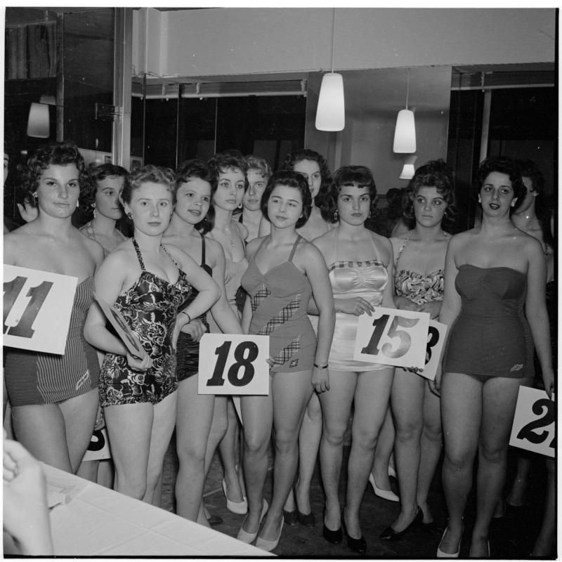 Models stehen in einer Gruppe im Badeanzug, halten Nummern in der Hand. Wahl für Miss Vienna von Scheidl