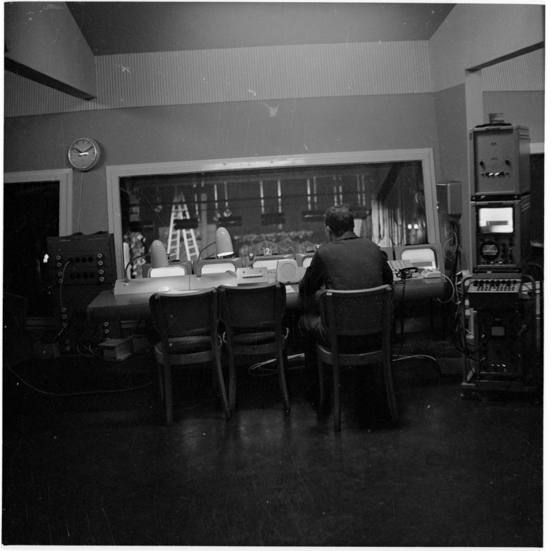 Mann in einem Studio sitzt mit Lautsprecher, Mischpult und diversen technischen Geräten. Fernsehstudio im Ronacher von Scheidl