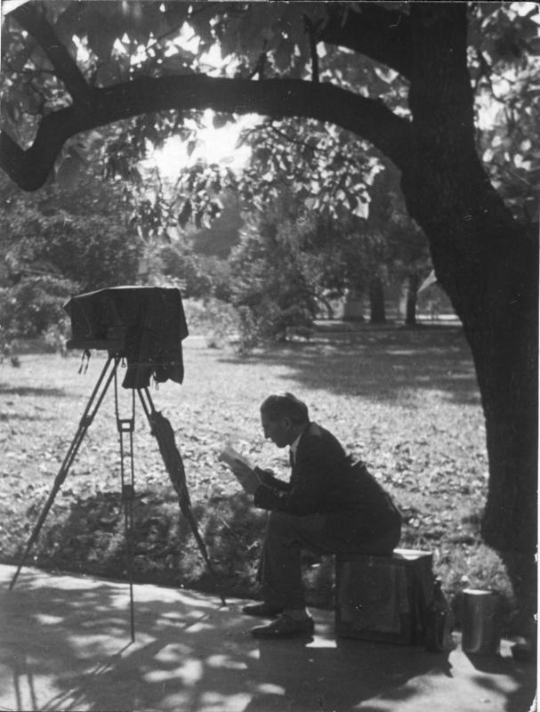Rudolf Spiegel auf einer Kiste im Park sitzend, etwas lesend, vor ihm die aufgebaute Kamera