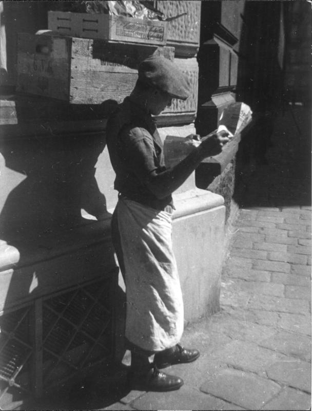 Junger Mann mit Schirmmütze vor einem Haus stehend, eine Zeitung lesend