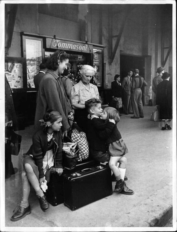 Frau mit drei Kindern, der Großmutter und Gepäck am Bahnsteig, im Hintergrund weitere Reisende und ein Lebensmittel-geschäft