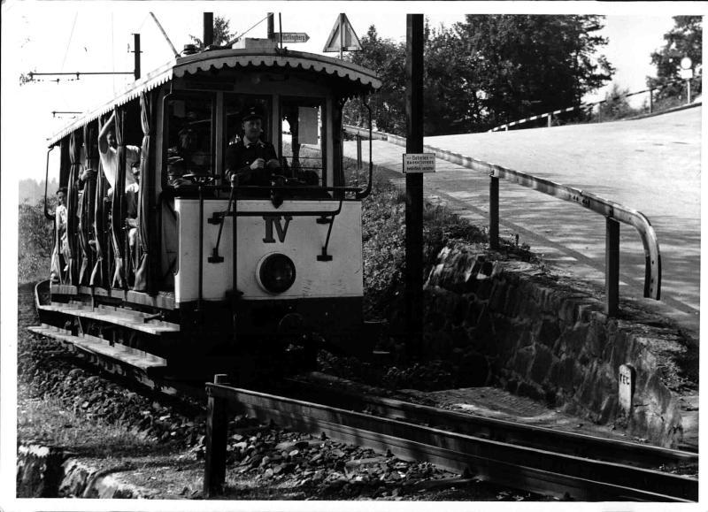 Offener Wagen der Pöstlingberg-zahnradbahn, Lokführer im Führerstand, einige Touristen sehen aus dem Wagen