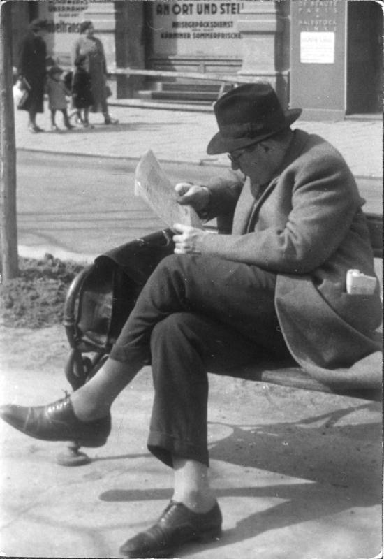 Mann sitzt auf einer Bank und liest die Zeitung
