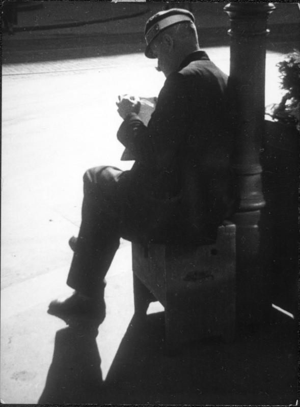 Straße, Dienstmann auf einem Schemel sitzend, eine Zeitung lesend