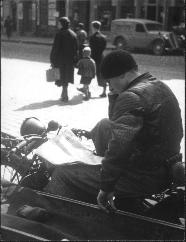 Junge Frau auf einem Motorrad sitzend, Zeitung lesend, dahinter Passanten
