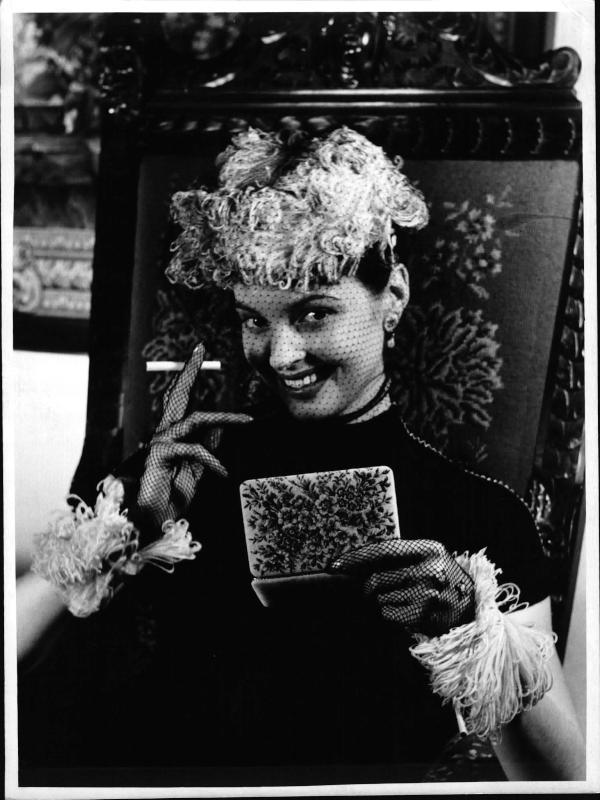 Petit Point - Stickerei, Jolles Studio, Modell Nadja Tiller mit einer bestickten Zigarettendose, vor einem bestickten Sessel