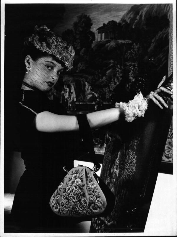 Petit Point - Stickerei, Jolles Studio, Modell Nadja Tiller mit einer bestickten Handtasche, vor einem Petit Point-Wandteppich