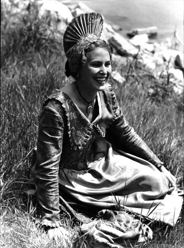 Trachten - Wachau, Frau in Wachauer Tracht mit Goldhaube, in einer Wiese sitzend, lachend