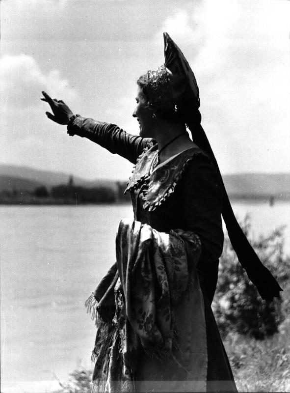 Trachten - Wachau, Frau in Wachauer Tracht mit Goldhaube, trägt einen Umhang über dem Arm, winkt Richtung Donau