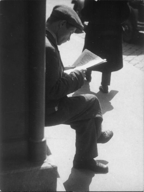 Mann auf einem Mauervorsprung sitzend, Zeitung lesend
