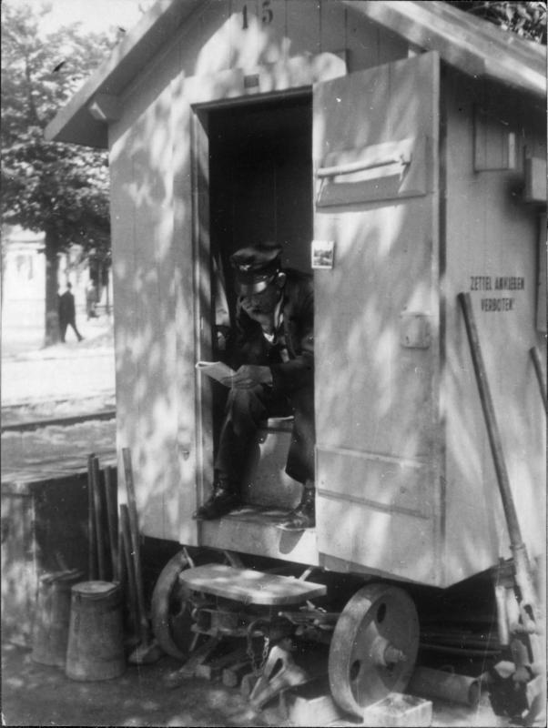 Parkwächter in einer Fahrbaren Holzhütte sitzend, Zeitung lesend