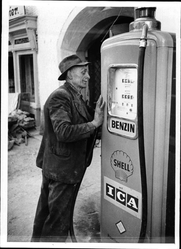 St. Wolfgang, ein alter Mann mit Hut steht an einer Tankstellen-zapfsäule und bedient sie