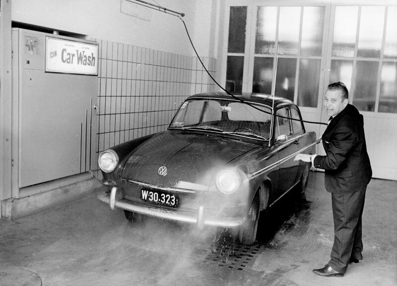 Erster Wagen-waschautomat Österreichs in der Touristen-tankstelle in Wien, ein Mann im Anzug wäscht seinen Wagen mit einem Hochdruck-reiniger, an der Seite ein Automat mit Aufschrift 'Coin Car Wash'