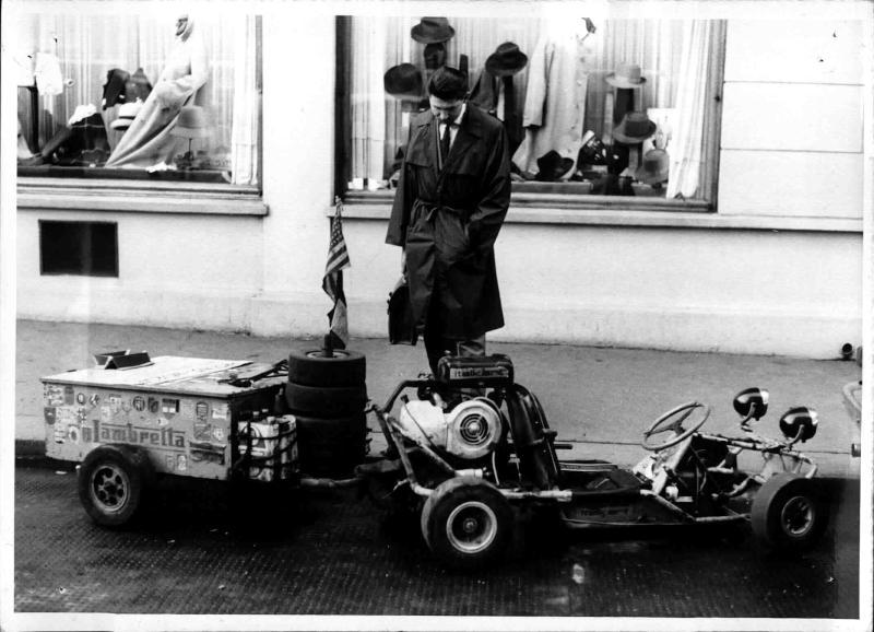 Ein Go-Cart mit Anhänger in Großaufnahme, dahinter steht ein Mann und betrachtet es, ein amerikanischer Student machte eine Weltreise mit diesem Fahrzeug