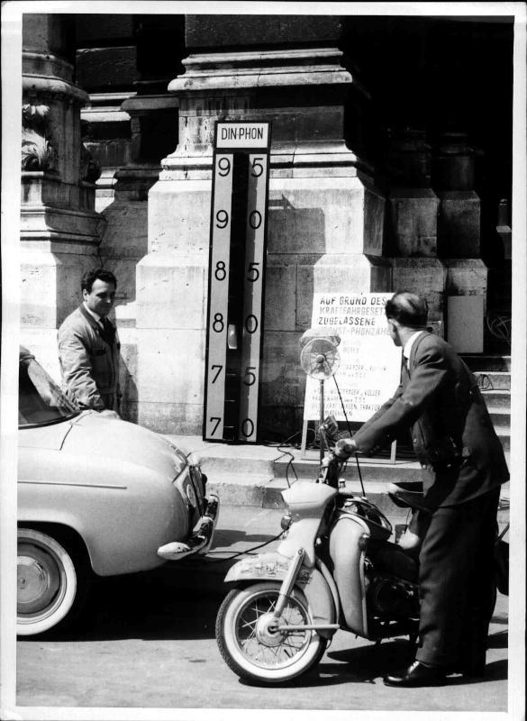 Lärmüberprüfung von Fahrzeugen auf dem Rathausplatz, ein Mann mit einem Auto, ein zweiter mit einem Motor-rad stellen sich an und messen die Phon-zahl ihrer Fahrzeuge, in der Mitte eine Mess-apparatur genannt 'DIN-PHON'
