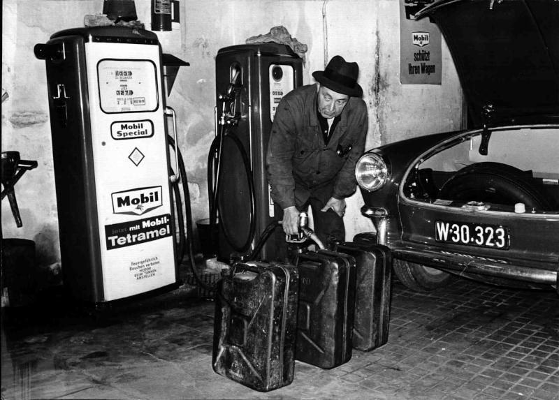 Tankstelle, ein Mann beim Betanken von drei Kanistern, dahinter die Zapfsäule, Versorgung mit billigem Benzin