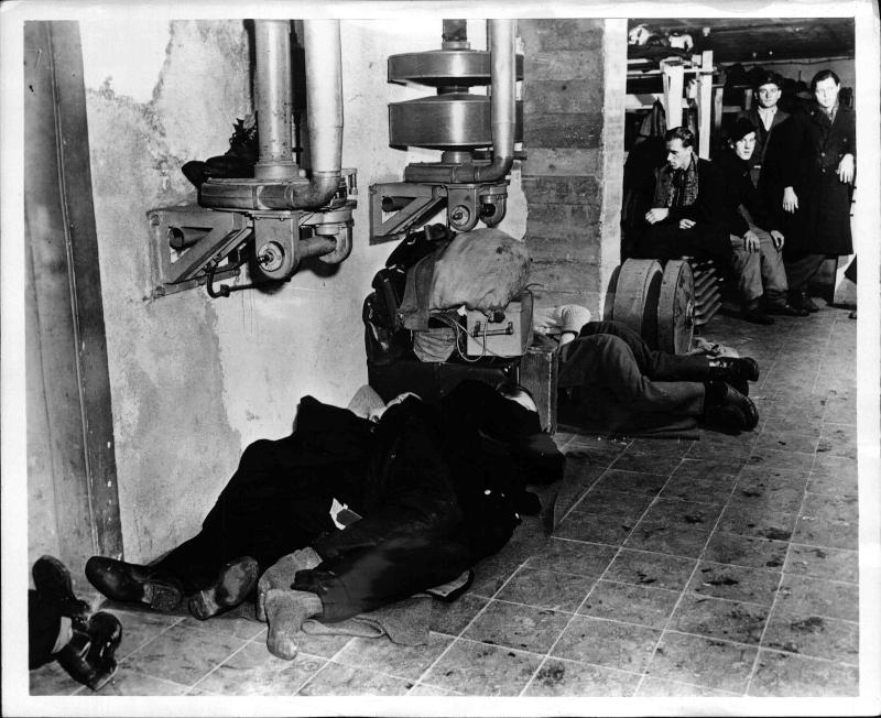 Obdachlose Männer liegen am Boden und schlafen, im Hintergrund ein weiterer Raum, wo Menschen sitzen und stehen, mit einigen Betten von New York Times Photo