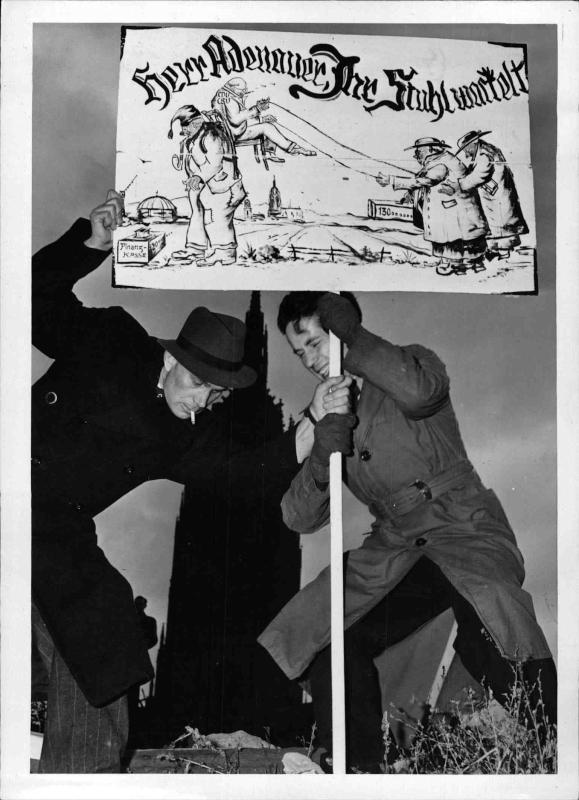 2. Protest-Treffen am frankfurter Römerberg Zwei Männer stellen ein Plakat auf mit einer Karikatur und der Aufschrift 'Herr Adenauer, Ihr Stuhl wackelt' von New York Times Photo