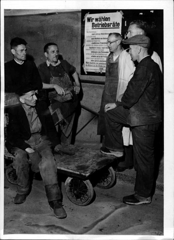 Parteien und Gewerkschaften Freier deutscher Gewerkschaftsbund, Arbeiter der Zeiss-Fabrik, im Hintergrund eine Tafel mit Schlagzeilen, die für den FDGB werben von New York Times Photo