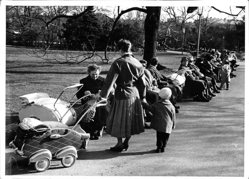 Frühling in Wien, Mütter mit Kindern und Kinderwagen im Park, ältere Menschen sitzen auf Parkbänken