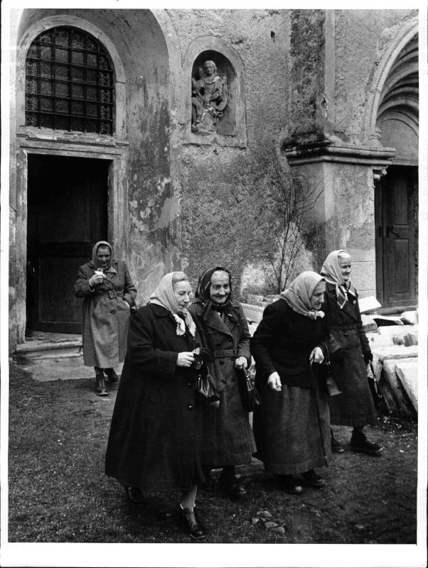 Fünf alte Frauen in dicken Winter-mänteln und Kopftüchern beim Verlassen einer Kirche