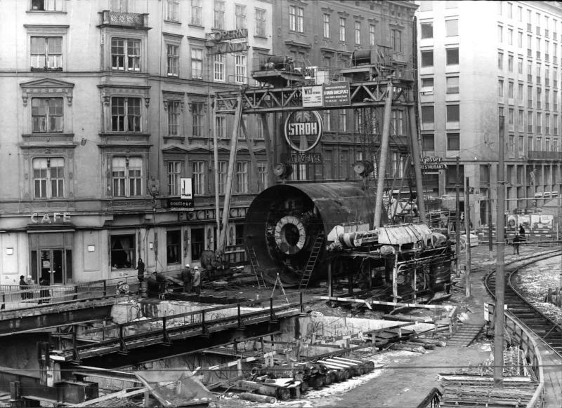 U-Bahn-Baustelle am Karlsplatz, Schildbohrmaschine hängt an einem Kran, davor einige Bauarbeiter, Baugrube