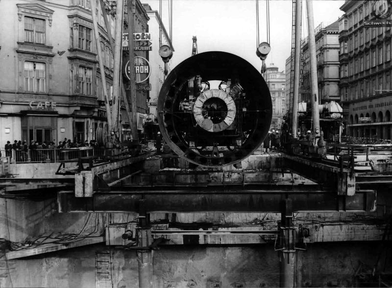 U-Bahn-Baustelle am Karlsplatz, Schildbohrmaschine wird in die Baugrube hinunter gelassen, Borhmaschine von vorne, an den Seiten einige Schaulustige, Bauarbeiter