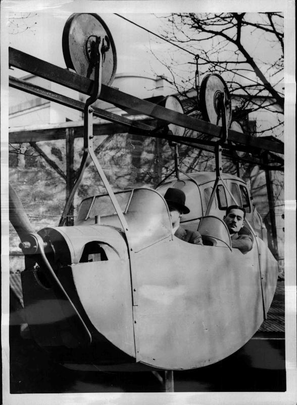 Verkehr, Kuriositäten Zwei Männer fahren in einem 'aufgehängten Flugzeug' wie mit einer Seilbahn von New York Times Photo