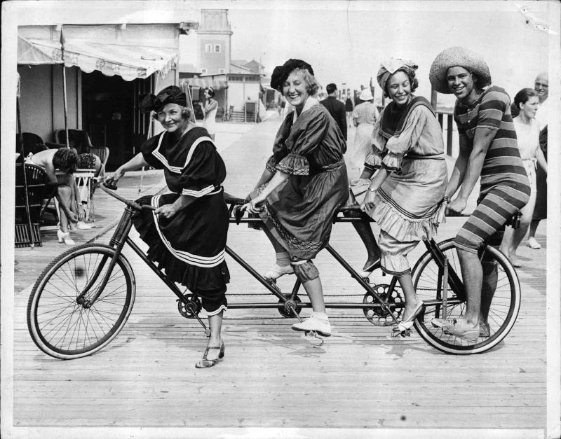 Mode: Bademode drei Frauen und ein Mann auf einem Rad für vier Personen, sie sind mit lustigen Bade- und Strandanzügen bekleidet von New York Times Photo