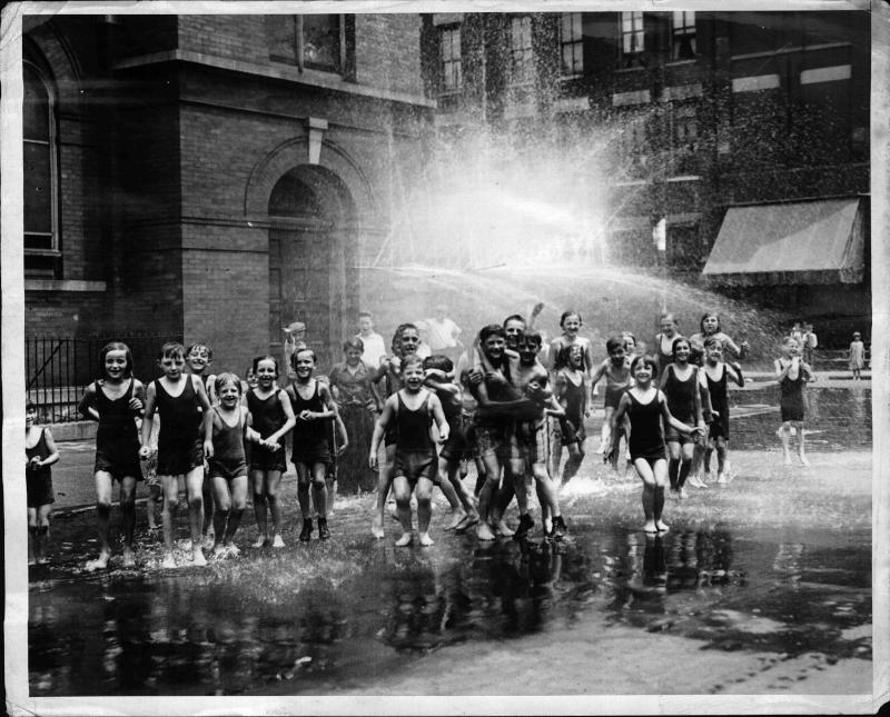 Eine Gruppe von Kindern im Baeanzug, die sich während der Hitzewelle von einem Hydranten anspritzen lassen von New York Times Photo