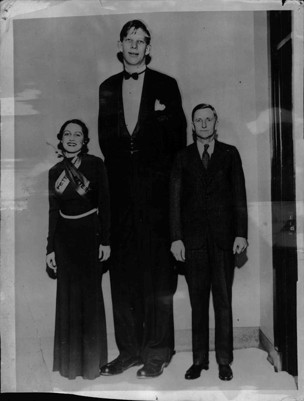 Robert Wadlow, der größte Mensch der Welt mit einer Länge von 2, 63m, neben zwei normalgroßen Menschen von New York Times Photo