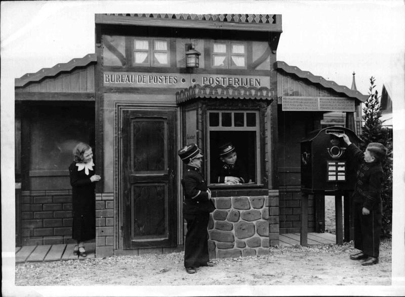 Die Stadt der Liliputaner bei der Ausstellung in Brüssel, das Post-Büro, zwei Postmänner, ein Zwergwüchsiger wirft Post in den Postkasten, Frau schaut zu von New York Times Photo