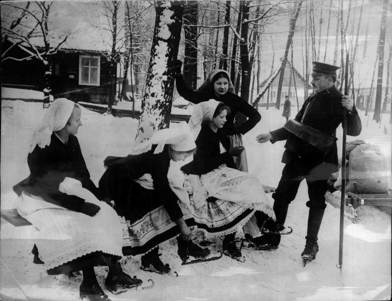 Foto aus dem Spreewald, ein Priefträger auf Schlittschuhen trägt die Post aus, vier in Tracht Frauen ziehen sich gerade Schlittschuhe an von New York Times Photo