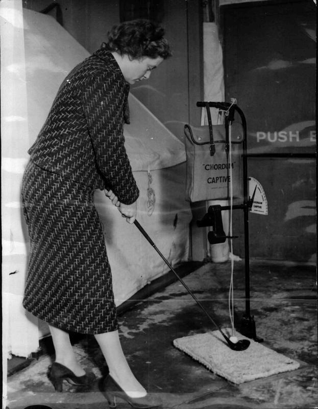 Britische Industrie-Ausstellung, Frau demonstriert ein Heim-Golf-Spiel, der Ball ist an einer Schnur befestigt von New York Times Photo