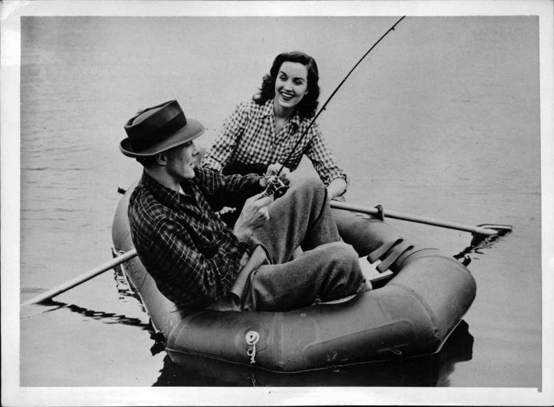 Ein Mann und eine Frau sitzen in einem Schlauchboot und angeln von New York Times Photo
