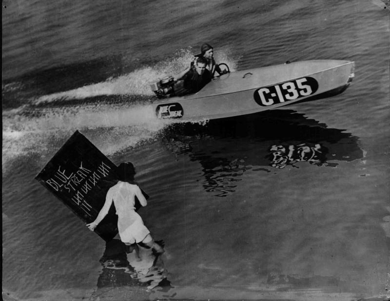 Motorboot erhält Signale von der Box, Frau steht mit einer Tafel im Wasser von New York Times Photo