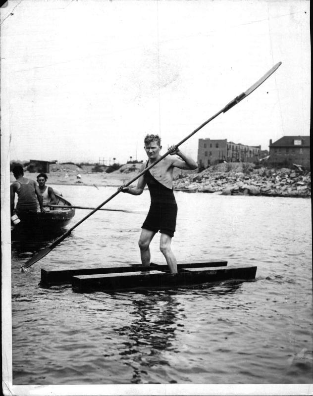 Mann auf pfostenartigen Wasser-Schiern mit einem Paddel in der Hand, daneben zwei Männer in einem Boot von New York Times Photo