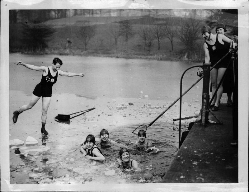 Frau im Badeanzug beim Eislaufen auf einem gefrorenen See, andere Frauen schwimmen in einem Eis-Loch von New York Times Photo